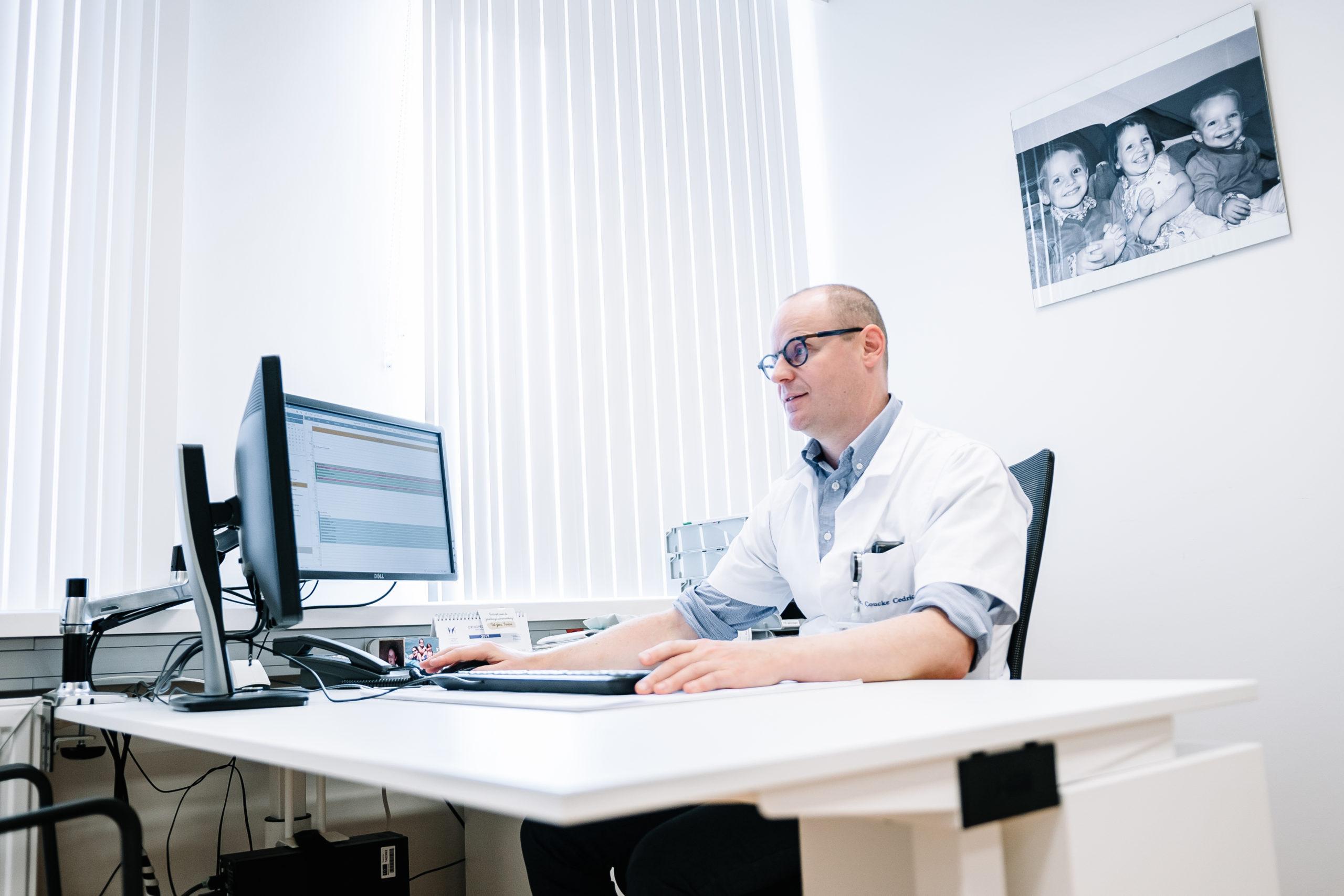 dr coucke achter bureau aan het werken